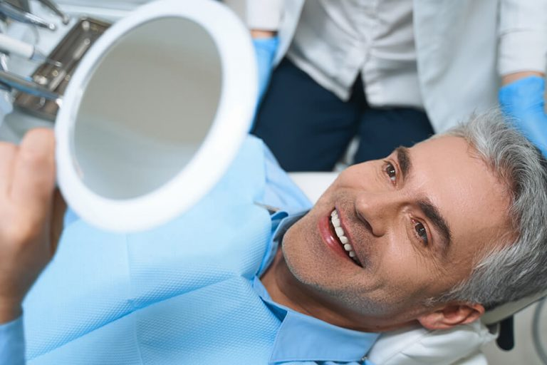 A male dental patient lays back in a dental exam chair and admires his smile in a handheld mirror during a cosmetic dentistry visit