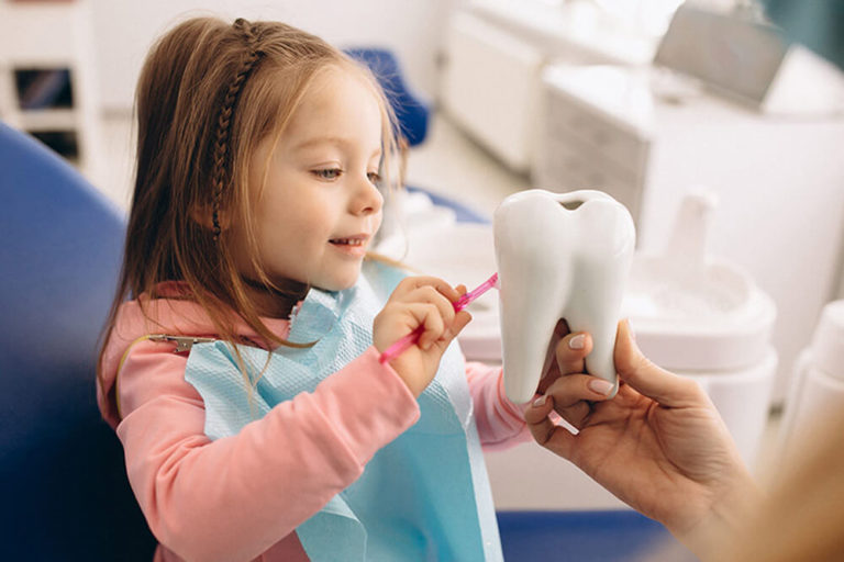 A pediatric dental patient sits in an exam chair and learns how to brush her teeth